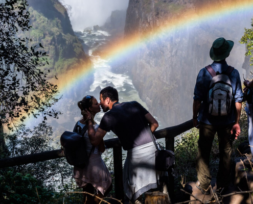 A couple embracing against the backdrop of the Victoria Falls, Zimbabwe